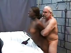 image Two dominatrixes inflict pleasurable pain on restrained male slave in a dungeon